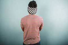 Young man in striped shirt and checkered hat Stock Images