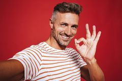 Young man in striped t-shirt smiling and showing ok sign while t royalty free stock images
