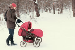 Young man strolling pushchair with baby in winter park. Young man strolling pushchair with baby in winter snow-covered park outdoors with copy space Royalty Free Stock Photography