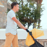 Young man strolling a pushchair Stock Photography