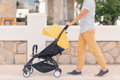 Young man strolling pushchair with sleeping baby. Young man strolling pushchair with a baby by the city street. Street cafe on background Royalty Free Stock Photos