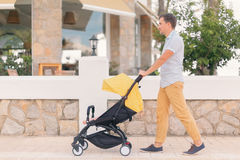Young man strolling pushchair with sleeping baby. Young man strolling pushchair with a baby by the city street. Street cafe on background Stock Photos