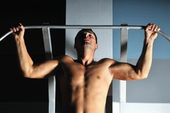 Young man with strong arms working out in gym Stock Images