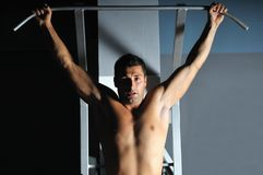 Young man with strong arms working out in gym royalty free stock photography