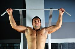Young man with strong arms working out in gym Royalty Free Stock Photo