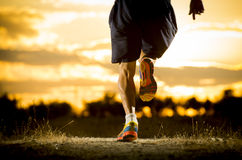 Young man strong legs off trail running at amazing summer sunset in sport and healthy lifestyle. Close up image of young man strong legs off trail running at Royalty Free Stock Images