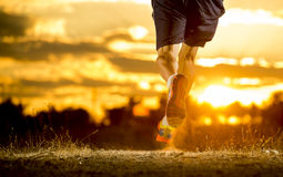 Young man strong legs off trail running at amazing summer sunset in sport and healthy lifestyle. Close up image of young man strong legs off trail running at Royalty Free Stock Photography