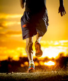 Young man strong legs off trail running at amazing summer sunset in sport and healthy lifestyle Stock Photos