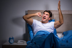 The young man struggling from noise in bed. Young man struggling from noise in bed stock image