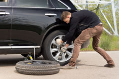 Young man struggling to change his car tyre. As he battles with a wheel spanner to loosen the nuts on the hub standing putting his weight behind the effort Stock Photos