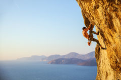 Young man struggling to climb challenging route on cliff. At sunset stock photo