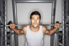Young Man Struggling To Lift Weights Stock Photo