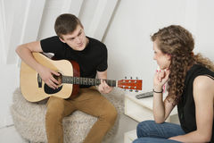 Young man strumming guitar besides female friend Royalty Free Stock Images