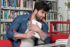 Angry Man With Too Much Paperwork to Do. Young Man Student Feel Bored While Trying to Studying Entry Exams to University or College Stock Photos