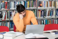 Bored Student With Books in Library. Young Man Student Feel Bored While Trying to Studying Entry Exams to University or College Royalty Free Stock Images