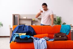Young man student preparing for trip at home