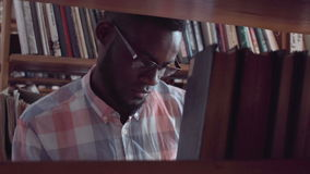 Young man student searching for book in library