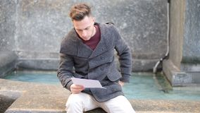 Young man sitting by fountain reading paper sheets in city setting. Young man, a student, sitting by fountain reading paper sheets in city setting in a winter stock video footage