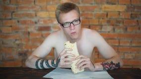 Young man, student sitting at home eating fast food. Shawarma, Shawarma, Shawarma. Healthy or unhealthy fresh food. Young man, student sitting at home eating stock footage