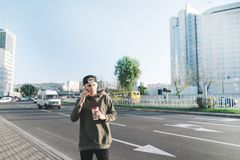 A young man is a student talking on the phone and holding a glass of coffee while walking around the city. Lifestyle and people co. Happy young man talk on phone Stock Images