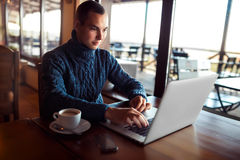 Young man. Student using tablet computer in cafe Royalty Free Stock Photos