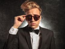 Young man in studio wearing tuxedo while fixing sunglasses Royalty Free Stock Photos