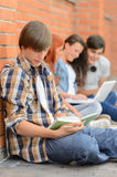 Young man studying book friends in background Stock Photography