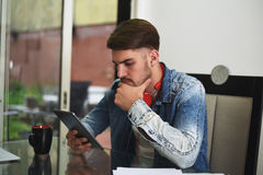 Young man studying with his tablet, headphones and coffee Stock Photo