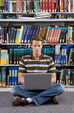 Young man studying in library, sitting with crossed legs and laptop computer on floor Royalty Free Stock Image