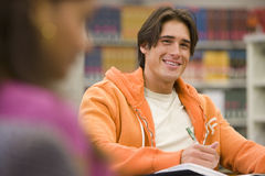 Young man studying in library, smiling, portrait Royalty Free Stock Image