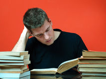 Young man studying, surrounded by books Stock Photo