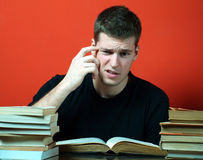 Young man studying, surrounded by books Royalty Free Stock Photography