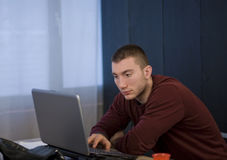 Young man studying and working on his laptop Royalty Free Stock Image