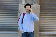 Young man talking on mobile phone. Young man of style hipster fashion talking on mobile phone stock image