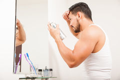 Young man styling his hair with spray. Profile view of a young man using hair spray to style his hair in front of a mirror in a bathroom Stock Photography