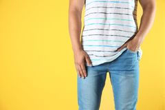 Young man in stylish jeans. On color background royalty free stock photography