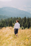 Young man in stylish suit standing on summer field. Forest hills at background Stock Image