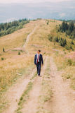 Young man in stylish suit walking on trail by summer field with hills at background Stock Image