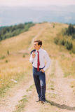 Young man in stylish suit walking on trail by summer field with his blazer over shoulder. Forest hills at background Royalty Free Stock Image