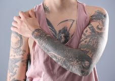 Young man with stylish tattoos on grey background. Closeup royalty free stock photo