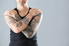 Young man with stylish tattoos on grey background. Space for text royalty free stock photo