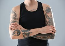 Young man with stylish tattoos. On grey background royalty free stock image