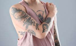 Young man with stylish tattoos. On grey background royalty free stock photos