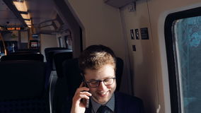 Young man and successful businessman traveling by the train speaks by smartphone. Young man and successful businessman traveling by the train sitting near the stock footage