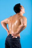 Young man suffering from back pain. Muscular young man clutching his lower back, suffering from back pain Stock Photos