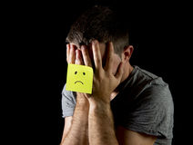 Young man suffering depression and stress alone with sad face post it note Royalty Free Stock Photography
