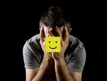 Young man suffering depression and stress alone with smiley face post it note. Young man suffering depression and stress sitting alone in pain and grief feeling royalty free stock photos