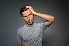 Young man suffering from a headache, a gesture of annoyance. Royalty Free Stock Images