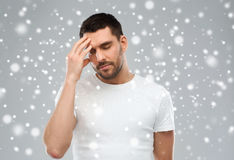 Young man suffering from headache over snow Stock Photography