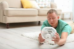 Young man suffering from heat in front of small fan. At home royalty free stock image